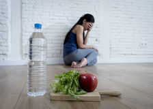 Woman or teenager girl sitting on ground alone worried at home suffering nutrition eating disorder. Young woman or teenager girl sitting on ground alone and Stock Photography