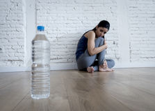 Woman or teenager girl sitting on ground alone worried at home suffering nutrition eating disorder Stock Image