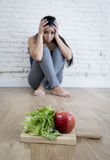 Woman or teenager girl sitting on ground alone worried at home suffering nutrition eating disorder Stock Photo