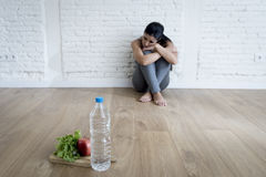 Woman or teenager girl sitting on ground alone worried at home suffering nutrition eating disorder Royalty Free Stock Photography