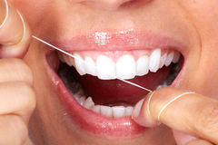 Woman teeth with dental floss. Stock Photography