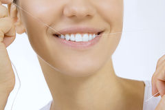 Woman and teeth floss. Young caucasian woman flossing her teeth (close up woman smile Royalty Free Stock Images