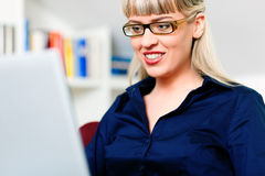 Woman telecommuting using laptop. Woman sitting in front of a bookshelf, working with a laptop in the internet from home, she is a telecommuter stock images