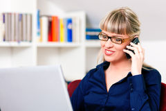 Woman telecommuting using laptop and phone. Woman sitting in front of a bookshelf using her telephone, working with a laptop in the internet from home, she is a stock photo