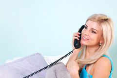 Woman on the telephone. Young blond woman sat in an armchair talking on the telephone Stock Photos