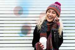 Woman with Telephone and Coffee in Hand Laughing stock photo