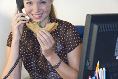 Woman on telephone at desk with sandwich, smiling, portrait stock image