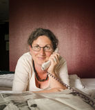 Woman on telephone in front of newspaper on bed. Woman on corded telephone reading glasses, newspaper Royalty Free Stock Images