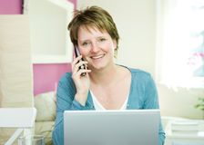 Woman with telephone and notebook computer Royalty Free Stock Photos