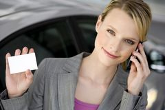 Woman telephoning. Beautiful young blonde woman telephoning, having a card in hand Stock Image