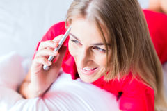Woman telephoning on bed. With smartphone Stock Photos