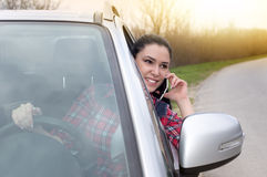 Woman telephoning in the car. Young pretty woman stopped car by the road and talking on the cell phone Stock Photos