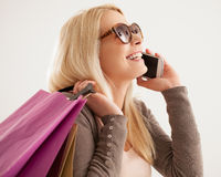 Woman Telephoning While Shopping. Portrait of a young Caucasian women making a phone call while shopping Royalty Free Stock Images