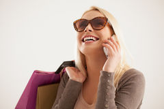 Woman Telephoning While Shopping. Portrait of a young Caucasian women making a phone call while shopping Royalty Free Stock Photography