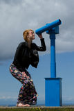 Woman and telescope. A beautiful woman in floral pants and black leather leather jacket looks through a blue telescope Stock Photos