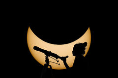 Woman with telescope Safe Solar Eclipse observation. Real Sun in the background. Observing Solar Eclipse through a telescope and a special filter to reduce royalty free stock photo