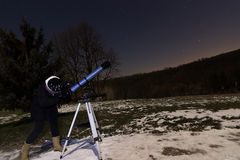 Woman with telescope under winter night sky Woman looking through telescope under starry night. Stock Image