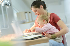 Woman teleworking on laptop with her baby Royalty Free Stock Image