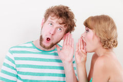 Woman telling an astonished man some secrets Royalty Free Stock Images