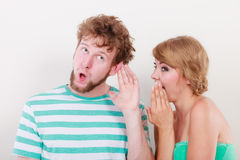 Woman telling an astonished man some secrets Royalty Free Stock Photos