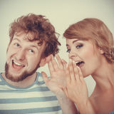 Woman telling an astonished man some secrets Royalty Free Stock Photo