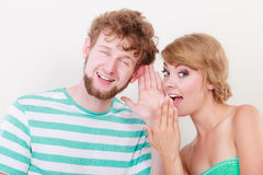 Woman telling an astonished man some secrets. Closeup women telling an astonished surprised men some secrets, couple talking royalty free stock images