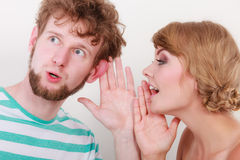 Woman telling an astonished man some secrets. Closeup women telling an astonished surprised men some secrets, couple talking royalty free stock photo