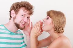 Woman telling an astonished man some secrets. Closeup women telling an astonished surprised men some secrets, couple talking royalty free stock image