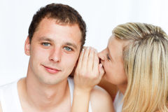 Woman telling her boyfriend something in the ear Royalty Free Stock Photo