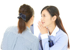 Woman telling secret to her friend Stock Photography