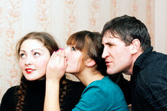Woman telling secrets. A girl whispers in my ear the secret of her friend and the guy overhears Stock Photo