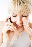Woman telling secrets on phone. A close up view of a young blond woman telling her friend a secret as she talks on her cellphone royalty free stock images