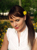 Woman with tellow daisy. Beautiful woman in a park with a daisy in her hair Stock Photos
