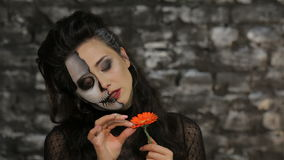 A woman tells fortunes tearing petals. Beautiful woman with make-up skeleton posing on black background of a brick wall. Halloween concepts and costumes stock video footage