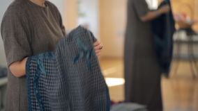 The woman tells and shows how to tie a long scarf around the neck. Teacher in a long gray dress in the classroom holding a large textile trendy checkered scarf stock footage