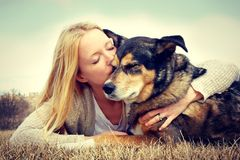 Woman Tenderly Hugging and Kissing Pet German Shep. A young woman and her German Shepherd dog are laying outside in the grass, and she is lovingly hugging and Royalty Free Stock Photos