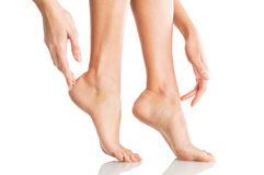 Woman tenderly touches her feet Royalty Free Stock Image