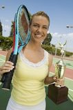 Woman on tennis court with Tennis Rackets and Trophy portrait Stock Images