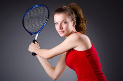 Woman tennis player against dark background Royalty Free Stock Image