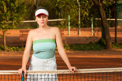Woman tennis player holding racket near netting Stock Photo