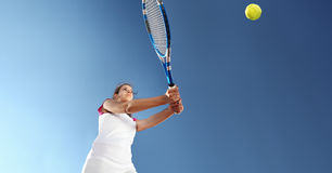 Woman tennis player with racket during a match game, isolated. On blue sky Royalty Free Stock Images