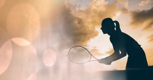 Woman tennis player silhouette and peach bokeh transition. Digital composite of Woman tennis player silhouette and peach bokeh transition Stock Image