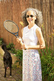 Active senior woman with tennis racket and dog stock images