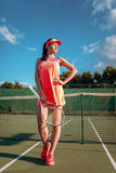 Woman with tennis racket poses on outdoor court Royalty Free Stock Photo