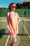 Woman with tennis racket poses on outdoor court Stock Photo