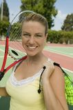 Woman with Tennis Racket and Tennis Balls on tennis court portrait Royalty Free Stock Photo