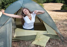 Woman tent camping. Young woman on camping awaking early morning in a tent stock photography
