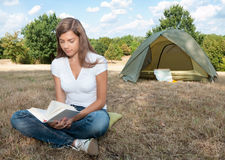 Woman tent camping book. Young woman at campsite with book in her hands and tent in background royalty free stock image
