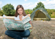Woman tent camping map. Young woman with map in her hands and tent in background stock photography