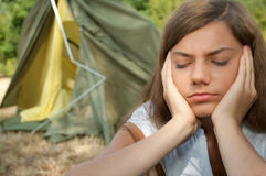 Woman tent trouble. Young woman frustrated with unfinished tent in background royalty free stock photography